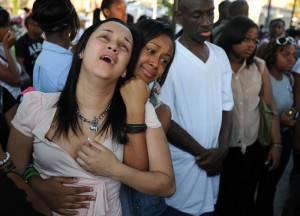 Emotions run raw as mourners weep at a vigil for a 15-year-old Roxbury teenager killed in a midday stabbing near Dudley Square in Boston on Wednesday, July 11, 2012.