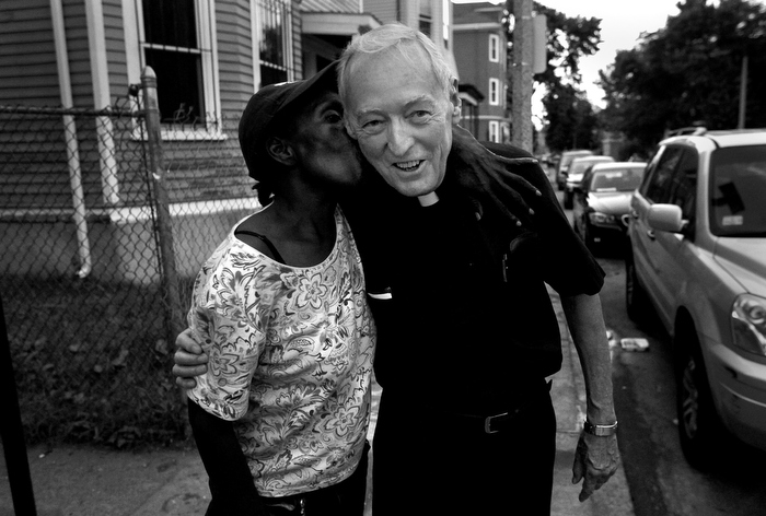 "Father ""Doc"" Conway of St. Peter's Church, gets a surprise kiss on his weekly Friday night walk through his neighborhood in Dorchester."