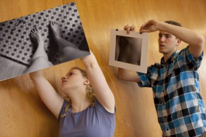 "An art exhibit called ""Body of Work"" focuses on body and body image. Kristen Cronon '12 (from left) and Arthur Bartolozzi '12 work together to hang the show in the Hilles Student Center at Harvard University."