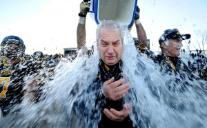 Framingham State football head coach Tom Kelley gets doused with cold water after his team defeated Salve Regina to clinch the the New England Football Conference championship at Bowditch Field in Framingham. The win gave the Rams a berth in the Div. 3 NCAA tournament.