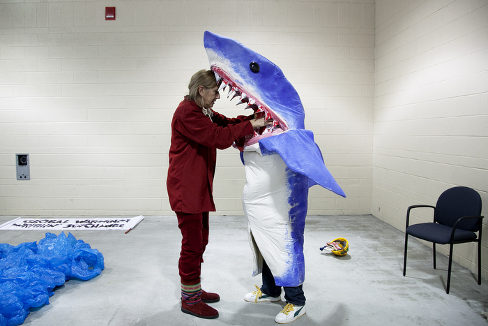 "Multi-discipline New York artist Pat Oleszko, left, helps Osmar Ramos-Caballero of Holyoke with his costume of a BP employee being eaten by a shark. Oleszko has a costume-themed ""Global Warning! Writhin' See/Change"" group that will march in the annual First Night Grand Procession. ÒIÕm hard-hearted and a realist, but I have a functional sense of humor, so thatÕs how I deal with negativity,Ó Oleszko says. Participants for First Night prepared the day before New Year's Eve in Boston, MA on Sunday, December 30, 2012."