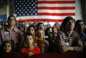 Audience members listen as Republican presidential nominee Mitt Romney speaks at a campaign rally in Cedar Rapids, Iowa October 24, 2012.