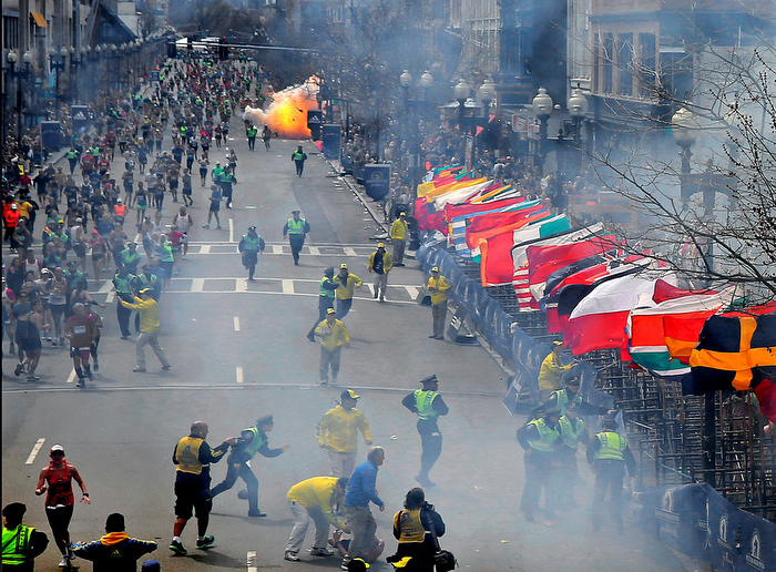 BOSTON, MA. 04/ 15 /13: MARATHON TERROR at the finish line, smoke still in place on the right from the first bomb explosion which killed one occurred at 2:50pm with police and others running to respond. A second bomb goes off in a fire ball that killed two more, 12 seconds later. In all hundreds were injured by the attack on the 117th Boston Marathon. In pursuit for 102 hours by police and agents that mounted the largest manhunt in regional history ended with the suspect terrorists Tsarnaev brothers, one killed in a shootout, the other captured hiding in a motorboat at a suburb backyard only miles away from the Boston crime scene.