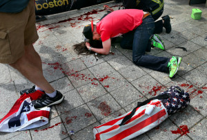 Boston-4/15/13- Joe Duncan, a Marine comforts a woman who was hit by shrapnel from the first terrorist bomb on the sidewalk near he finish line of the Boston Marathon on Boylston Street.