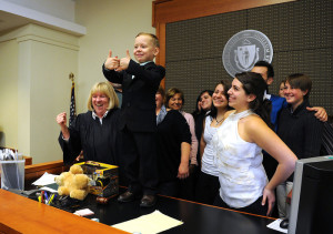 Bryce Almeida , 4, of Taunton, stands on top of the judges bench and  gives the thumbs-up signal at the conclusion of his adoption surrounded by family and friends during Southeastern Massachusetts National Adoption Day, at Brockton District Court, on Friday,  Nov. 22, 2013.