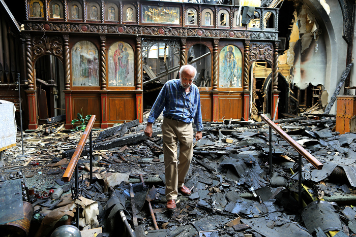South Boston-08/23/13 Tom Evangelou, the treasurer of St. John The Baptist Albanian Orthodox Church spent the day trying to recover church items that were damaged in a 5-alarm five on Tuesday that heavily damaged the church.  He walks through the remains of the altar.