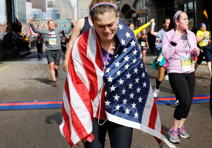 Samantha Herwig, of Salem reacts while crossing the finish line of the Run to Remember honoring fallen MIT Police officer Sean Collier in Boston, Massachusetts May 26, 2013. Herwig, who ran the Boston Marathon said she ran the last  six miles of the marathon with her friend who didn't get to finish, and today she was running for her.