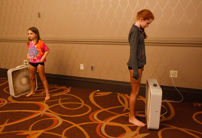 Girls competing in the World Irish Dancing Championships stand next to fans as they wait for their spray tans to dry in Boston, Massachusetts March 24, 2013.