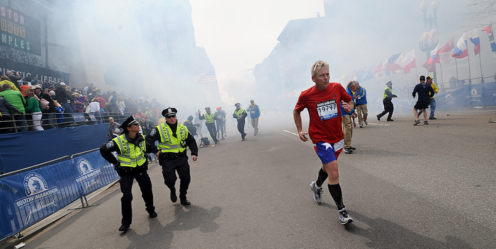 As smoke fills Boylston Street,  a runner reaches the finish line  and police begin to react moments after a bombing at the finish line of the 2013 Boston Marathon.