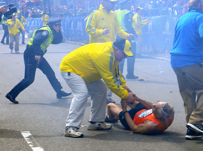 Bill Iffrig, 78, of Lake Stevens, Washington state, is assisted by a race official after collapsing as a Boston Police officer draws her weapon moments after a bombing at the Boston Marathon finish line on Monday, April 15, 2013.