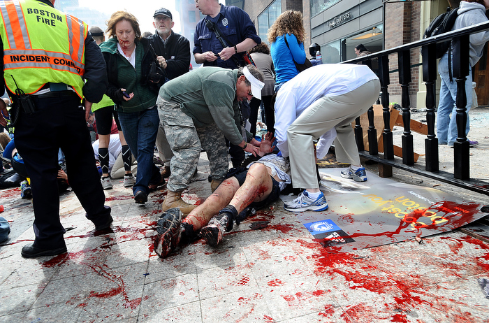 Good Samaritans  tend to injured spectators on the sidewalk of Boylston Street in Boston after a bombing near the finish line of the Boston Marathon on Monday, April 15, 2013.  Three people were killed and over 200 injured in the attacks.