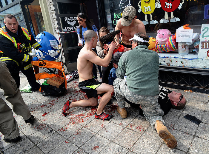 Boston marathon runner Robert Wheeler of Ashland, a  student at Framingham State University, kneeling at left, helps a man injured after the bombings at the Boston Marathon finish line.  Wheeler had just crossed the finished line and ran to the scene of the first bombing,  taking off his shirt to apply it to the man's wound and elevating the leg in an attempt to slow the bleeding.