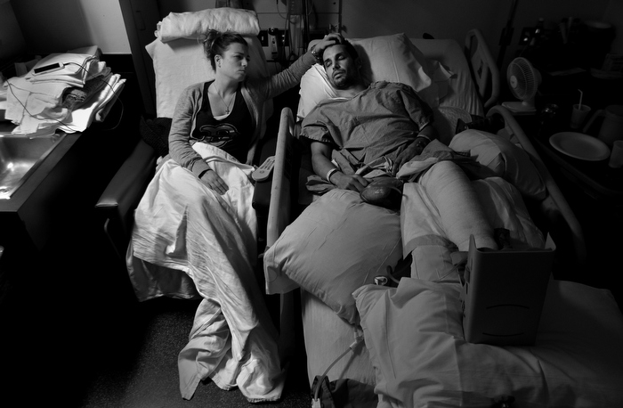Jen Regan, fiancŽe  of Boston Marathon bombing victim Marc Fucarile, strokes his forehead as he lay asleep in his hospital bed in Massachusetts General Hospital following his 7th surgery, three weeks after the attack. His right leg was amputated and the remaining one is badly damaged with a broken knee, shattered foot, third degree burns, and shrapnel wounds.