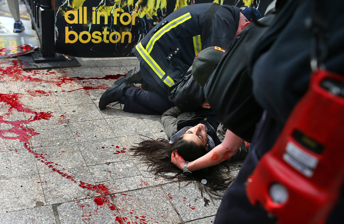 Boston-5/03/13- Sydney Corcoran from Lowell, Massachusetts lies next to her trail of blood as she is comforted on the sidewalk at the site of the first Boston Marathon bombing. She was standing with her mother Celeste and father Kevin to cheer on her aunt was was running. A piece of shrapnel the size of a cell phone from the pressure-cooker bomb severed her femoral artery. She nearly bled to death. She fell fifteen feet away from her mother who lost both legs in the bombing.