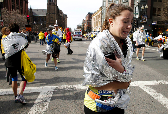 An unidentified Boston Marathon runner leaves the course crying near Copley Square in Boston Monday, April 15, 2013.