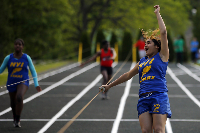 Kelsey Lora (R), from the New York Institute for Special Education, celebrates after winning the girls 75-yard dash at the 67th annual Eastern Athletic Association for the Blind track and field tournament hosted at the Perkins School for the Blind in Watertown, Massachusetts May 18, 2013.  Blind runners hold on to handles on wires to guide them down the track and help them stay in their lane.