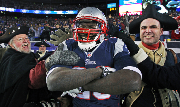 "Patriots running back LeGarrette Blount smiles and crosses his arms in satisfaction as he celebrates with members of the ""End Zone Militia"" (a group of Minutemen who fire their muskets after every New England score) following his touchdown run in the fourth quarter. The New England Patriots hosted the Pittsburg Steelers in an NFL regular season game at Gillette Stadium."