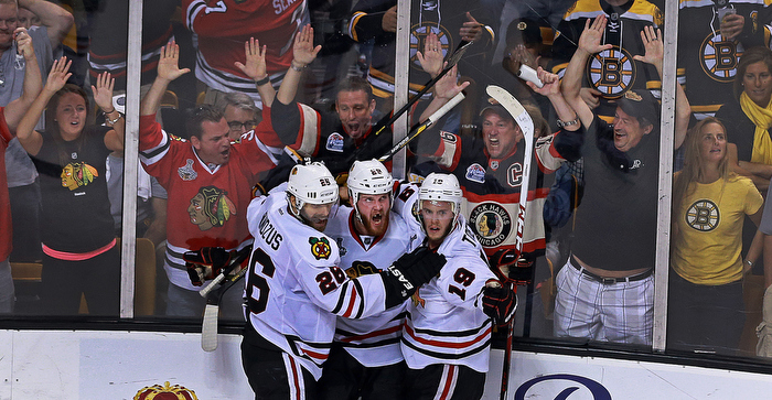 With less than 90 seconds left in the game, and the Blackhawks down by a goal, Chicago's Bryan Bickell (center) beat Bruins goalie Tuukka Rask  to tie the game at  2-2