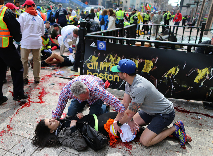 Boston-04/15/13- Sydney Corcoran from Lowell is helped by Matt Smith (left) from Boston and Zack Mione from Portland, Oregon on the sidewalk at the site of the first Boston Marathon bombing. They saved her life by applying pressure to her wounded leg and using t-shirts as a turniquet.