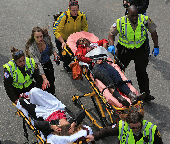BOSTON, MA. 04/ 15 /13:   Bomb victims Mery Daniel (right) and Victoria McGrath are pushed to safety on stretcher. Both suffered serious injurious to their legs:  Mery Daneil lost her left leg.