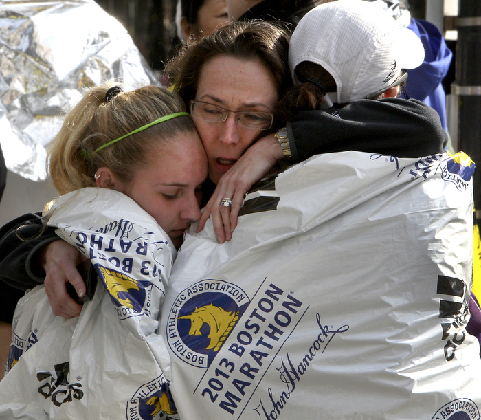 Boston, MA:  04-15-13:   Katherine Swierk (left) is reunited with her aunt Terry Days (center) and friend Jocelyn Cascio outside Copley Square in Boston after the explosions at the Boston Marathon.  Swierk was a race volunteer, Cascio ran the race, but was forced to withdraw at 25.6 miles due to the attack.