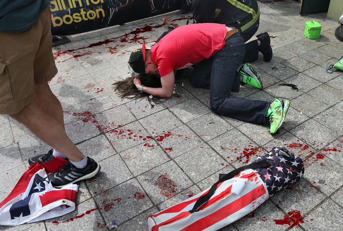 Boston-4/15/13- Joe Duncan, a Marine, comforts a woman who was hit by shrapnel from the first terrorist bomb on the sidewalk near the Boston Marathon finish line of Boylston Street.