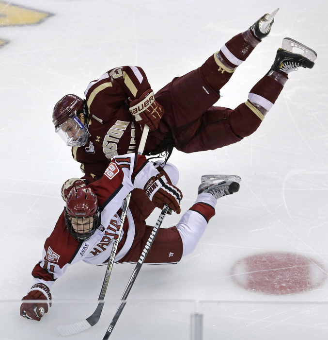 Boston College's Steven Whitney, top, and Harvard's Kyle Criscuolo go airborne as they collide during the first period of a Beanpot hockey tournament game in Boston, Monday, Feb. 4, 2013.