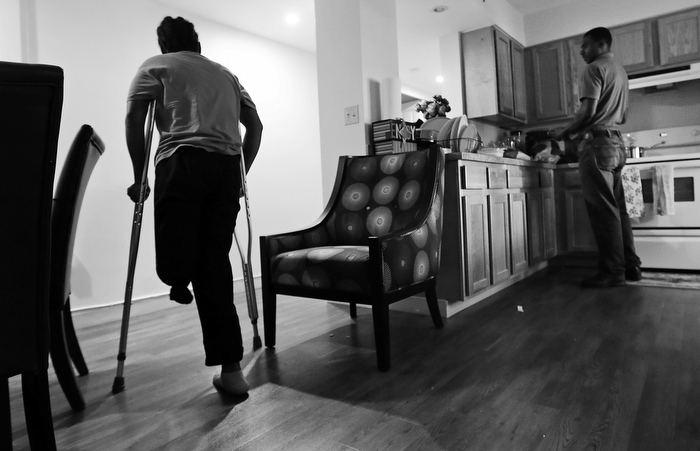 Mery Daniel, a Boston Marathon bombing survivor, uses crutches as she heads down a hallway in her home, while husband Richardson Daniel helps prepare dinner, Thursday June 20, 2013, in the South End neighborhood of Boston. Richardson Daniel, who had been a dermatologist in Haiti, works with a group helping Autistic children in Boston.  With his wife coping with her physical changes, Richardson has had to increase his other responsibilities in their family.