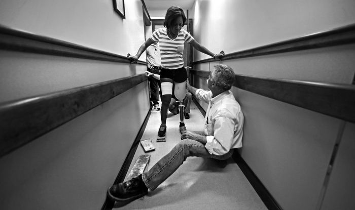 Paul Martino, of United Prosthetics, helps steady Mery Daniel, as she takes her first step since losing her left leg in the Boston Marathon bombings, while getting fitted for a prosthetic leg at the company in the Dorchester neighborhood of Boston, Tuesday, June 4, 2013.  Martino's family business has been helping amputees for about 100 years, including many of the bombing survivors.