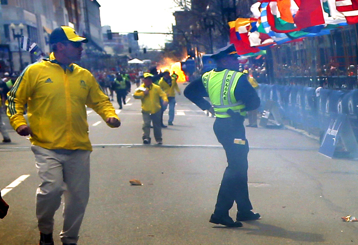Boston-4/15/13-  The second terrorist bomb explodes several blocks from the Boston Marathon finish line as Marathon volunteers and Boston Police react.