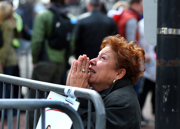 Boston-4/15/13- A woman kneels and prays at the scene of the first terrorist bomb near the finish line of the Boston Marathon on Boylston Street