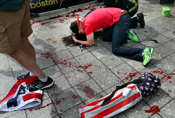 Boston-4/15/13- Joe,Duncan, a Marine comforts a woman who was hit by shrapnel from the first terrorist bomb on the sidewalk near he finish line of Boylston Street.