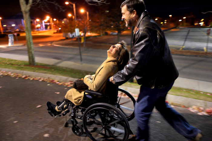 Lowell-11/9/13- Kevin and Celeste Corcoran make their way to the Tsongas Arena  to an event to honor victims  and first responders of the Boston Marathon. Celeste was tired from being on her legs all day and was wheeled the long distance from the parking lot.