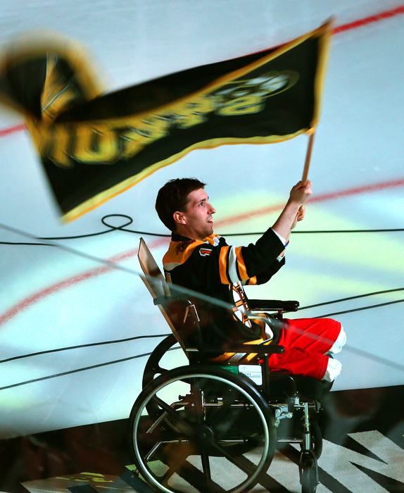 Boston-5/04/13-Boston Marathon bombing survivor Jeffrey Bauman waves a Bruins flag before the start of the Bruins vs Toronto Maple Leaf quarterfinal playoff game. He lost both legs in the bombing. He lost both legs in the bombing.
