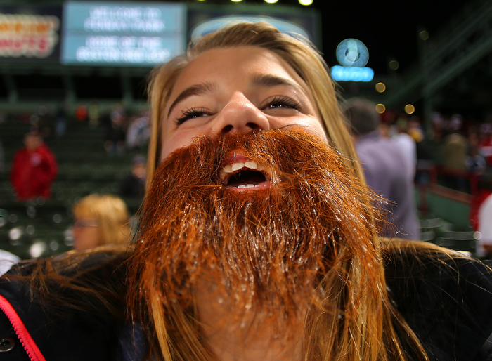 Boston-10/19/13-- ALCS game 6 Red Sox vs Tigers, Sox fan Kacie Smith,14 from Chicopee watches batting practice from the centerfield bleachers wearing a beard to honor the Red Sox.