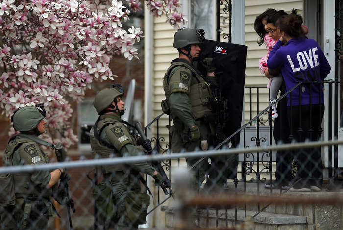 Residents clear out of their homes as police officers search house to house for the second suspect in the Boston Marathon bombings in a neighborhood of Watertown, Massachusetts April 19, 2013.  Two explosions hit the Boston Marathon as runners crossed the finish line killing at least three people and injuring over 100 others.