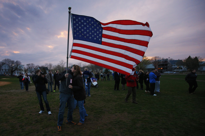 Neighbors hug under a U.S. flag as they arrive for a candle light vigil in the Dorchester neighborhood of Boston, Massachusetts April 16, 2013 where eight year-old Boston Marathon explosion victim Martin Richard lived.  News reports say that Martin Richard was one of the victims of two explosions which hit the Boston Marathon on Monday killing at least three people and injuring over 100 others.