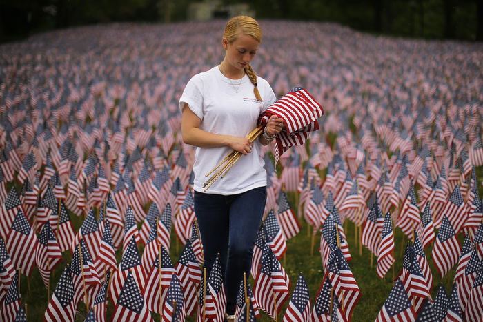 Shannon Day, a volunteer with Massachusetts Military Heroes Fund, replaces broken flags at a Memorial Day display of United States flags on the Boston Common in Boston, Massachusetts May 23, 2013.  According to the Massachusetts Military Heroes Fund, the flags are planted on the Common for fallen Massachusetts service members at the Memorial Day holiday, which will be celebrated May 27 in the U.S.