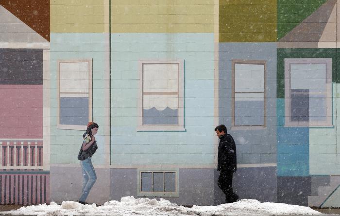 A pedestrian walks past a mural at the beginning of a winter storm in Somerville, Massachusetts March 7, 2013.