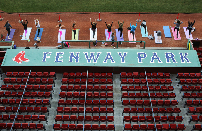 Participants take part in the first ever public yoga session at Fenway Park, home of MLB's Boston Red Sox, in Boston, Massachusetts September 23, 2013.  Money raised by the Fenway Yoga session benefited two of the Boston Red Sox foundation's cornerstone programs, the Red Sox Scholars Program and the RBI Youth Baseball and Softball Programs.