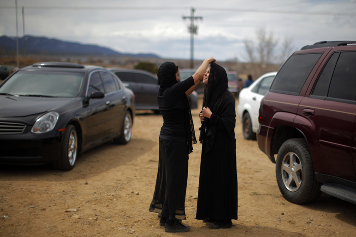 Girls, dressed for the role of Veronica, fix each other's veils between Good Friday religious ceremonies at the Morada de Talpa  in Talpa, New Mexico March 29, 2013.  A morada is an unsanctified chapel where the Hermanos, a centuries old lay Catholic group of men in northern New Mexico, worship.