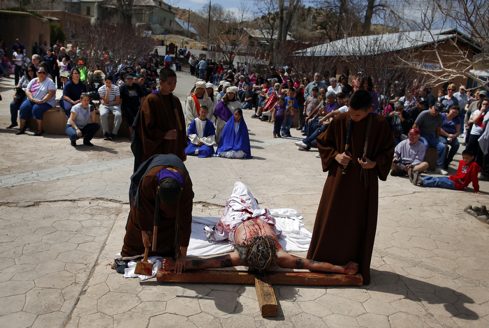 Students playing the roles of Roman soldiers place a man playing the role of Jesus (C) on a cross during a re-enactment of the Stations of the Cross at the Sanctuary of Chimayo in Chimayo, New Mexico March 28, 2013.  The students are part of a youth group from Our Lady of Sorrows church in Bernalillo, New Mexico which re-enacts the Stations of the Cross every year.