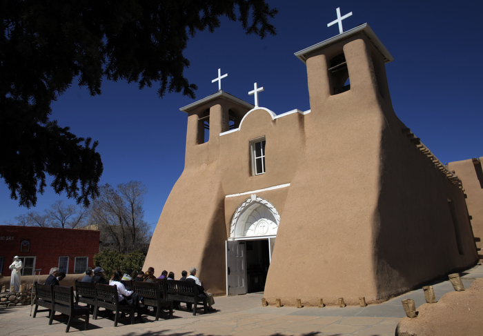 Parishioners sit in pews for Easter Mass outside the full San Francisco de Asis Catholic Church in Ranchos de Taos, New Mexico March 31, 2013.
