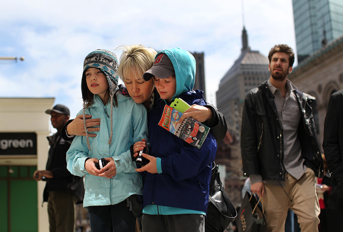 Boston, MA., 04/24/13, Boylston Street opens for the first time to the public since the bombs went off at the finish line of the Boston Marathon.  Tanya McIntyre brought her twins Tiana and Colten, 9, down to the site of the first bombing and said a prayer.