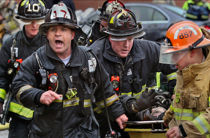 March 26, 2014-Boston,MA. Boston fire Lieutenant Sean O'Brien screams out for an ambulance as he and others rush injured firefighter Michael Kennedy from 298 Beacon St. after he and another firefighter were trapped in the large wind-whipped fire that would claim the building. Kennedy, who was barely alive at rescue, and fire Lt. Edward Walsh, died in the nine alarm fire.