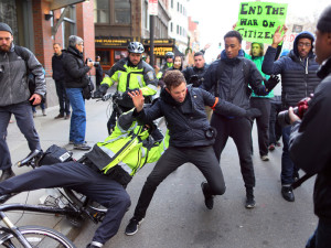 Boston--12/13/14- Thousands of protestors marched through the streets of Boston as part of the Black Lives Matter protest to bring attention to  the recent police killings of unarmed blacks.  A protestor is grabbed by a Boston Police officer on his bike after the protestor kicked his bike causing the officer to fall on Tremont Street. The police officer let him go.