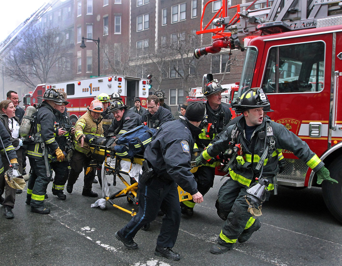 03/26/14: Boston, MA: Frantic rescuers look for an available ambulance as they try and save Boston Firefighter Michael Kennedy, who is on the stretcher after he was pulled out of the burning building in the background. He was rescued after being trapped by flames while battling the nine alarm fire. Kennedy later died at the hospital. The fire at  298 Beacon Street also claimed the life of Fire Lt. Edward Walsh, Jr.