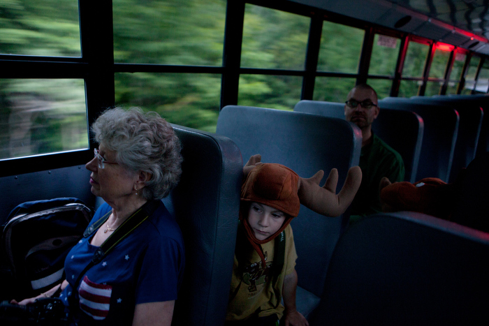 "L-R: Leslie Boggis, Henrik Axelson, 7, and Gus Axelson, ride on a bus during a moose searching tour that was organized through the North Country Moose Festival on August 22, 2014, in Millsfield, New Hampshire. The Axelson family traveled to New Hampshire and Vermont with the hope of sighting a moose, an activity known locally as ""moosing""."