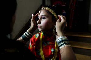 Manchester, NH Sunday, Aug. 31, 2014: A young Bhutanese girl's headdress gets a final adjustment before she heads on stage to dance during a Bhutanese Celebration honoring elders.