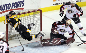 David Pastrnak, left, of the Providence Bruins, goes flying into the cross bar of Providence's goal as Portland goaltender Mike McKenna and defenseman Patrick McNeill, at right, look on during Portland's home opener at the Cross Insurance Arena Saturday, October 11, 2014. There was no goal on the play.